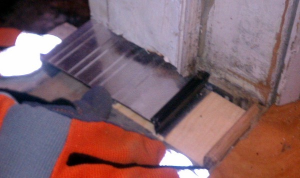 Checking the fit of the threshold in the freshly cut door frame