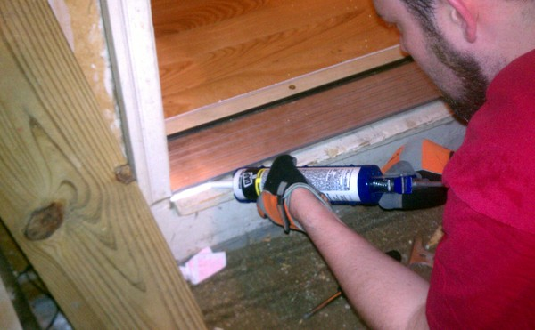 Caulking the gaps around the new door threshold
